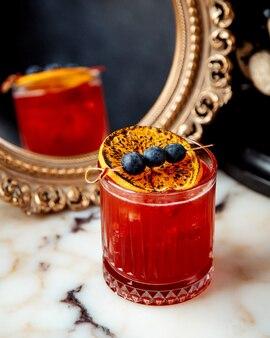Cocktail vermelho com limão e frutas