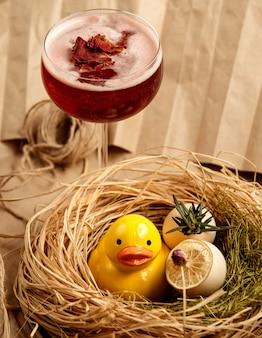 Cocktail vermelho decorado com pétalas de rosa secas ao lado de patinho de cerâmico amarelo