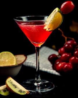 Cocktail vermelho em cima da mesa com uma fatia de limão