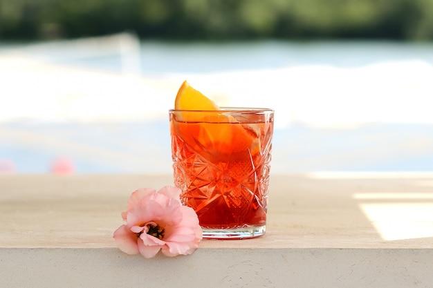 Cocktail vermelho em um vidro com uma fatia de laranja. com decoração de flores