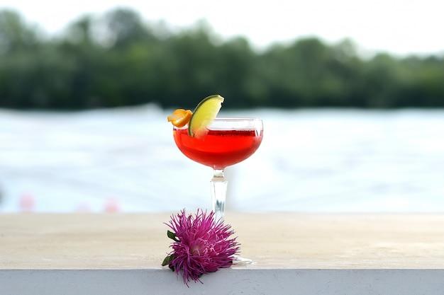 Cocktail vermelho em uma taça de vidro com uma fatia de cal. com decoração de flores