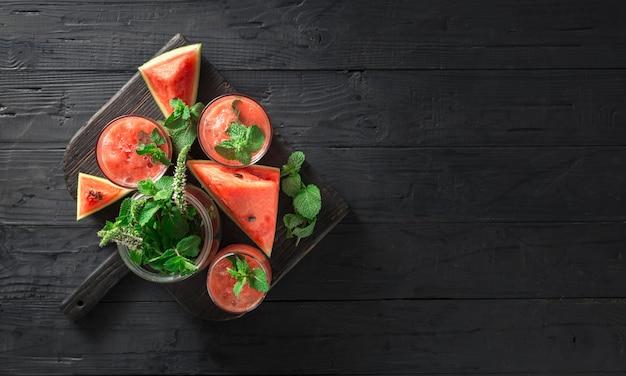 Cocktails bebe mojito de melancia em uma mesa de madeira escura
