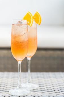 Cocktails com fatias de laranja e cubos de gelo