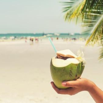 Cocktails de coco fresco com mãos de mulher na praia tropical - férias no verão. estilos de cores vintage