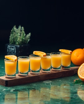 Cocktails laranja em copos pequenos.
