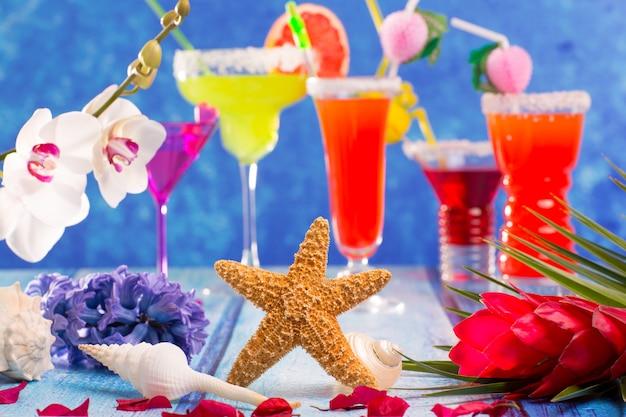 Cocktails misturados coloridos em madeira azul tropical