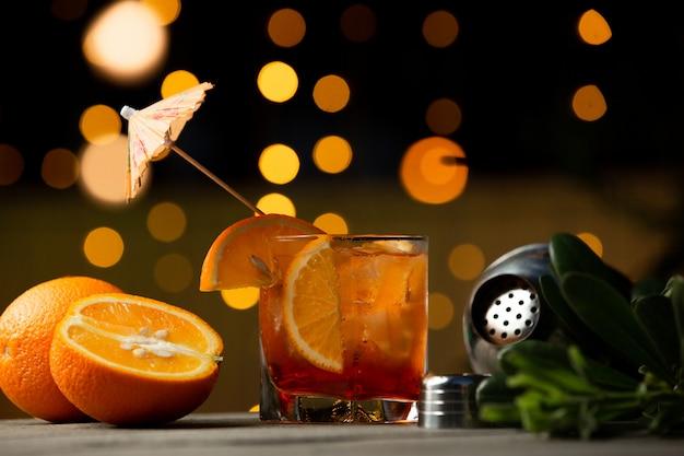 Cocktain de suco de laranja em vidro com cubos de gelo.