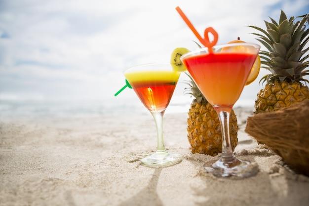 Coco, abacaxi e dois copos de bebida cocktail mantido na areia na praia tropical