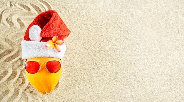 Coco amarelo fresco em um chapéu de papai noel com óculos de sol na areia