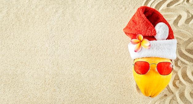 Coco amarelo fresco em um chapéu de papai noel vermelho com óculos de sol vermelhos na areia