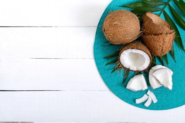 Coco. coco inteiro, casca e folhas verdes em uma mesa de madeira branca. noz grande. coco de frutas tropicais com casca. spa. foto de comida. fundo da foto.