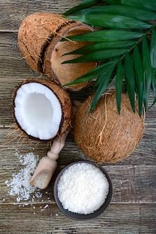 Coco. coco inteiro, casca, flocos de coco e folhas verdes numa superfície de madeira. noz grande. coco de frutas tropicais com casca. spa. a vista de cima