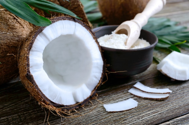 Coco. coco inteiro, casca, flocos de coco e folhas verdes numa superfície de madeira. noz grande. coco de frutas tropicais com casca. spa. fechar-se