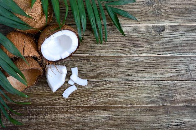 Coco. coco inteiro, casca, flocos de coco e folhas verdes numa superfície de madeira. noz grande. coco de frutas tropicais com casca. spa. fundo da foto. frutas tropicais de textura. copie spase.