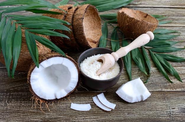 Coco. coco inteiro, casca, flocos de coco e folhas verdes numa superfície de madeira. noz grande. coco de frutas tropicais com casca. spa.