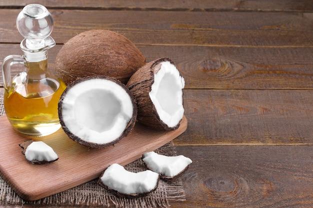 Coco com fatias de coco e óleo de coco em um fundo de madeira marrom
