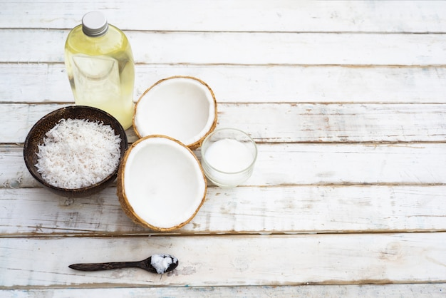 Coco com óleo de coco na garrafa no fundo da mesa branca
