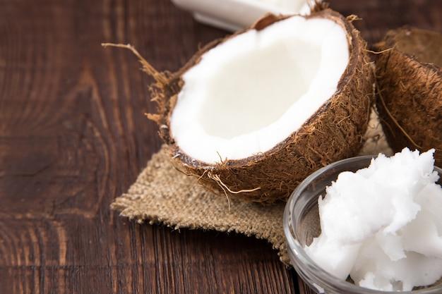 Coco com óleo de coco no pote em fundo de madeira