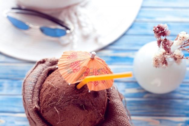 Coco com palha e chapéu branco com óculos de sol azuis por trás