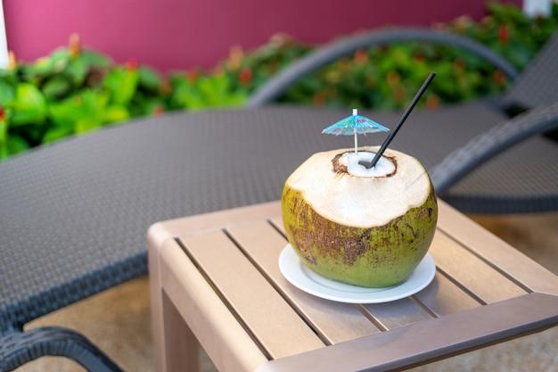 Coco com um canudo em uma mesa de madeira