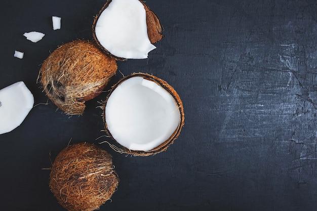 Coco cortado ao meio em um fundo preto