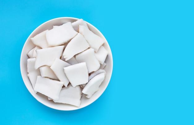 Coco cortado em pedaços em uma tigela na superfície azul