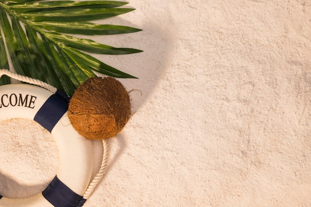 Coco de folha de palmeira e bóias de vida na areia