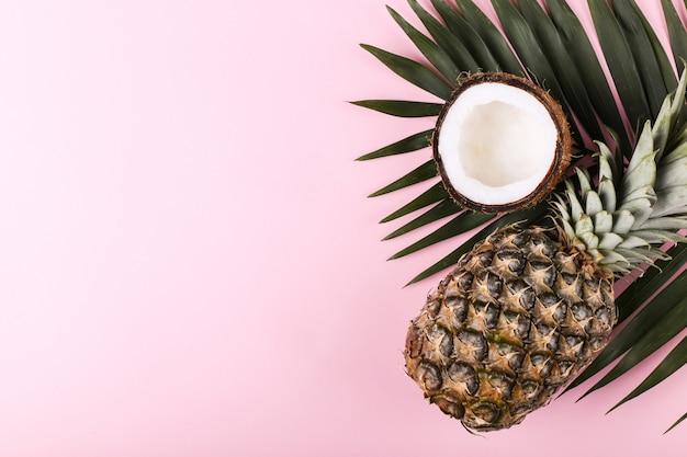 Coco e abacaxi na cor. clima de verão, copie o espaço.