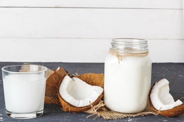 Coco e copo de leite de coco em fundo de madeira