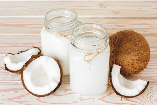 Coco e copo de leite de coco no fundo de madeira