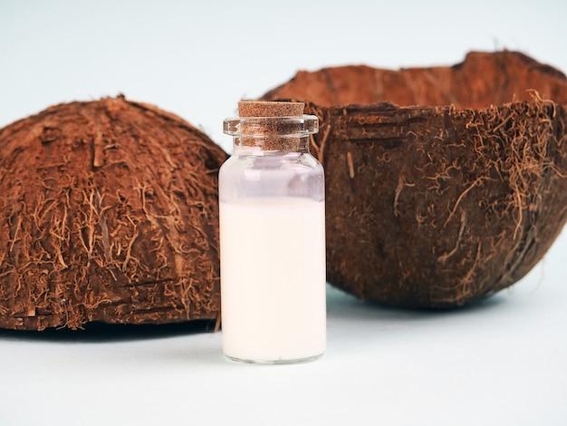 Coco e leite de coco na mesa azul. óleo de coco com noz fresca. leite de coco, óleo de aparas em tubo de ensaio para pesquisa, superalimento, óleo natural, cosméticos.