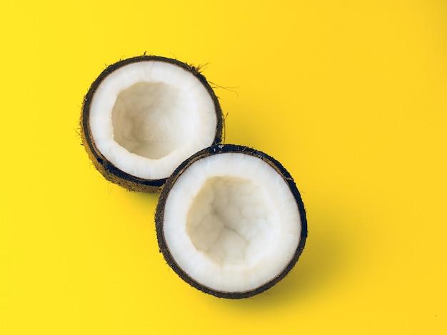 Coco em fundo de cor amarela, planta plana, vista superior