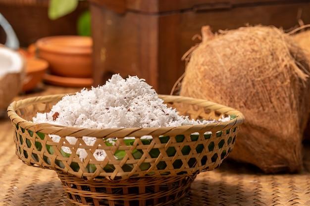Coco em pó de um coco na cesta na mesa dentro da cozinha para fazer leite de coco