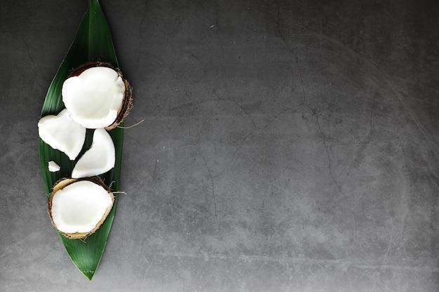 Coco em uma mesa de pedra escura. óleo de coco e batatas fritas.