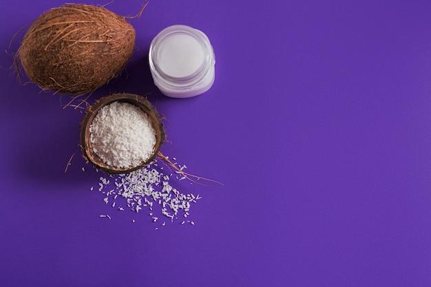 Coco, flocos de coco e óleo de coco em frasco em fundo roxo. conceito de culinária saudável. vista superior com espaço para texto
