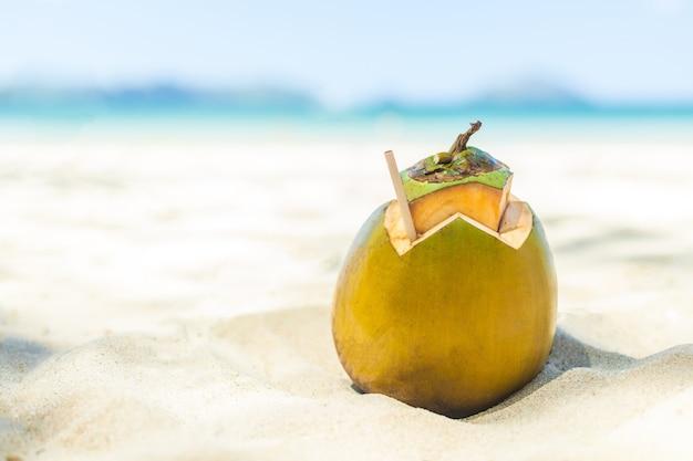 Coco fresco e jovem deitado na areia da praia com canudo pronto para beber