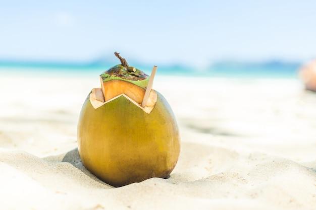 Coco fresco jovem deitado no fundo da praia de areia com canudo pronto para beber. conceito de viagens de férias tropicais