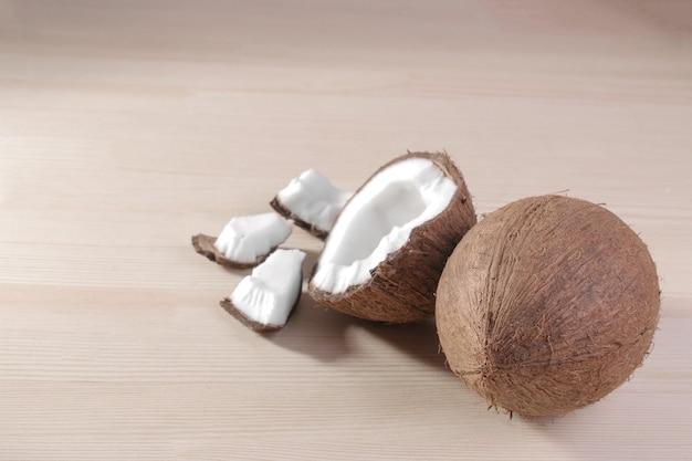 Coco grande fresco e pedaços de coco em um fundo de madeira natural