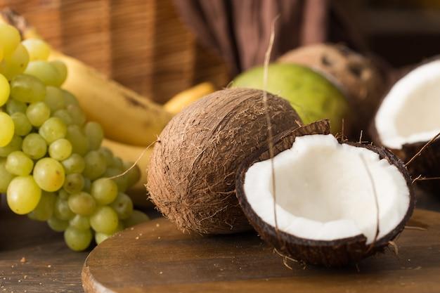 Coco inteiro e quebrado ao lado do outro, uva, manga, banana