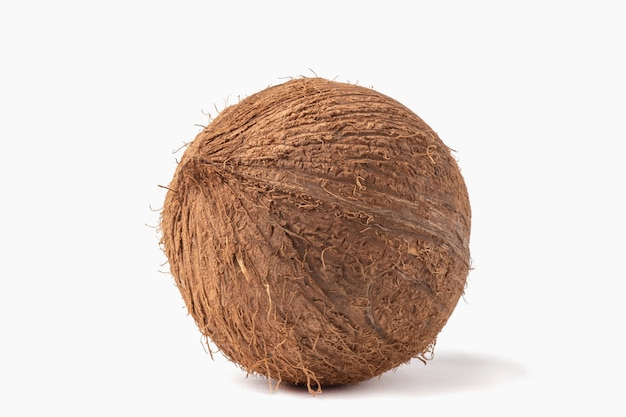 Coco inteiro maduro isolado no fundo branco.