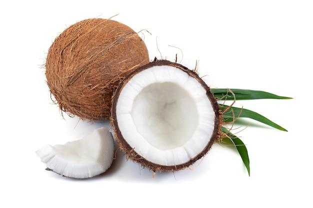 Coco inteiro, pedaços com uma folha tropical verde em uma superfície branca.