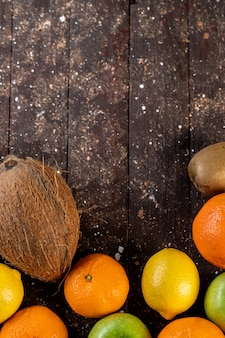 Coco limão maçã e tangerina em uma mesa de madeira