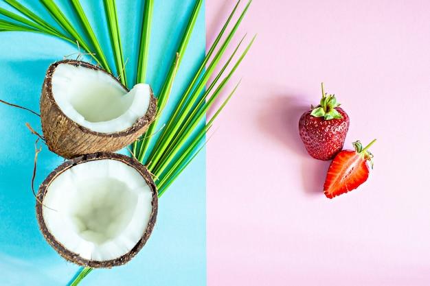 Coco maduro com morangos frescos e folhas de palmeira em um fundo azul e rosa. conceito saudável e conceito de spa.