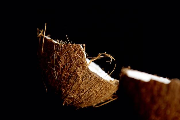 Coco maduro é dividido em duas metades isoladas em um preto