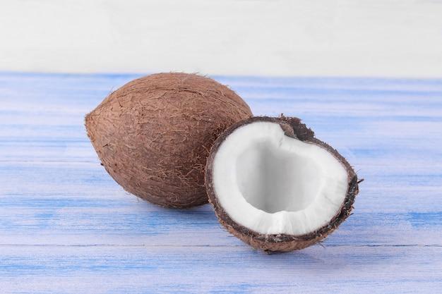 Coco marrom grande e meio coco em uma mesa de madeira azul sobre um fundo branco
