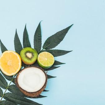 Coco meio cortado; limão; laranja e kiwi em folhas verdes contra o fundo azul