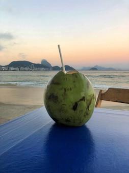 Coco na mesa. ao fundo a praia de copacabana.