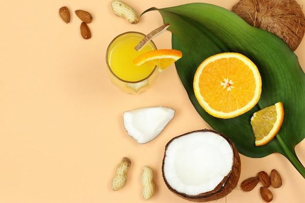 Coco, nozes e suco de laranja, folha de palmeira sobre fundo bege