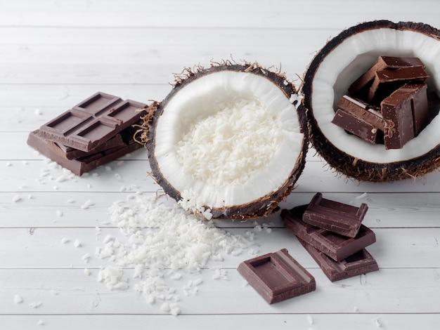 Coco orgânico fresco quebrado em duas partes com coco em um fundo de madeira rústico