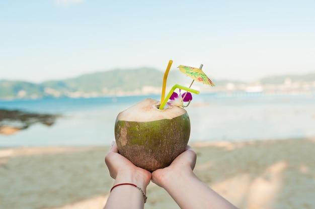 Coco pendurado na palmeira com praia de areia amarela no fundo